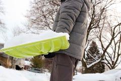 VMan, das Schnee vor seinem Haus im Vorort schaufelt und entfernt stockfoto