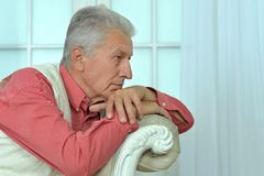 VMature man sitting in vintage sofa Stock Photo