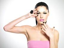 Vända mot av den härliga kvinnan med svart spikar och rosa kanter Royaltyfri Foto