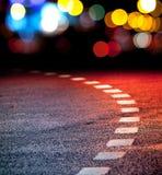Vändande asfaltväg med markeringslinjer och lampor Fotografering för Bildbyråer
