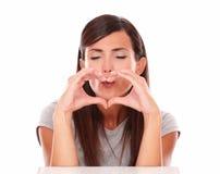 Vänlig flicka som gör en gest förälskelse och blåser en önska Arkivfoton