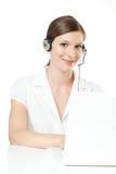 Vänlig ung kvinna med hörlurar med mikrofon och bärbara datorn Royaltyfri Foto