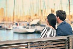 Vänner kopplar ihop datummärkning på bänk i hamnen Barcelona Fotografering för Bildbyråer