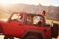 Vänner på vägturen som kör i konvertibel bil Fotografering för Bildbyråer