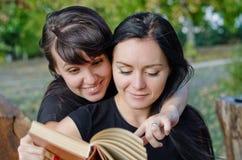 Vänner som delar en boka Fotografering för Bildbyråer