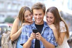 Vänner som delar massmedia i en smart telefon Arkivbilder