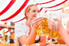 Vänner som dricker bayerskt öl på Oktoberfest Arkivbild
