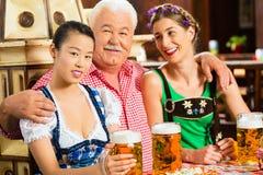 Vänner som dricker öl i bayersk bar Royaltyfri Foto