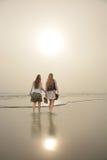 Vänner som går på den härliga dimmiga stranden på soluppgång Arkivbild