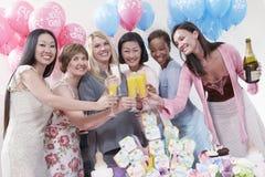 Vänner som har ett rostat bröd på baby shower Arkivbild