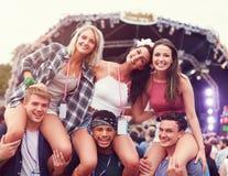 Vänner som har gyckel i folkmassan på en musikfestival Royaltyfri Foto
