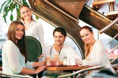 Vänner som har gyckel på ett kafé Royaltyfri Foto