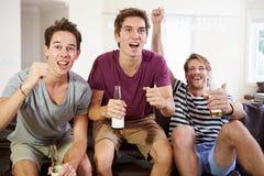 Vänner som håller ögonen på sporten fira mål Arkivbild