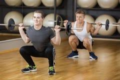 Vänner som lyfter skivstången, medan huka sig ned i idrottshall Royaltyfria Bilder