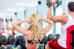 Vänner som lyfter vikter i konditionidrottshall Arkivbilder