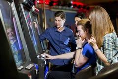 Vänner som spelar i en kasino som spelar springan och olika maskiner Arkivbild