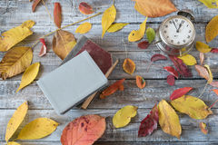 Vntage books and clock on wooden table. Autumn composition. Stock Images