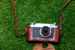 Vntage camera in case on spring green grass background Stock Photography