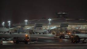 Vnukovoluchthaven bij de winternacht, Moskou Sneeuwploegvrachtwagens die tarmac schoonmaken stock video