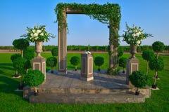 Voûte de mariage décorée du tissu et des fleurs dehors Belle installation de mariage Cérémonie de mariage sur la pelouse verte da Image libre de droits