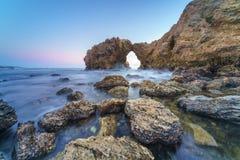 Voûte, falaise et plage naturelles de roche Photographie stock