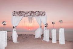 Voûte de mariage avec la composition florale avec le rideau blanc sur le sunse Image libre de droits