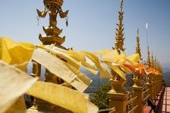 Voando e acenando bandeiras budistas amarelas e alaranjadas no templo tailandês com fundo do céu Fotos de Stock Royalty Free