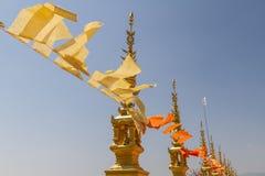 Voando e acenando bandeiras budistas amarelas e alaranjadas no templo tailandês com fundo do céu Imagens de Stock Royalty Free