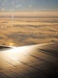 Voando em um plano de ar Wing Sunrise Golden Clouds Looking para fora uma janela imagem de stock