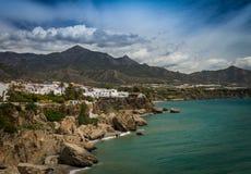 Você viu o grupo espanhol da costa A das casas brancas nos penhascos pelo mar com as montanhas no fundo imagens de stock royalty free