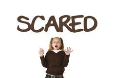 Vocabulario de la lengua inglesa que aprende la tarjeta de la escuela con la palabra asustada y la colegiala imagenes de archivo
