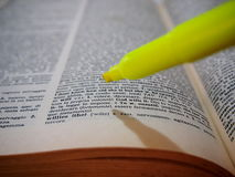 Vocabulary. Student studying for a language test using a dictionary and a yellow highlighter Stock Images