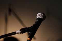 Vocal microphone. With stand on the stage with shadows on highlighted background royalty free stock photo
