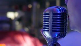 Vocalist con le labbra rosse che canta nel primo piano del microfono video d archivio