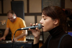 Vocalist girl is singing in studio. Keyboard player in out of focus Royalty Free Stock Photography