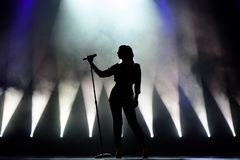 Vocalist singing to microphone. Singer in silhouette royalty free stock image