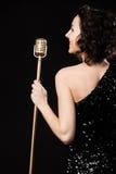 Vocalista moreno bonito da menina que sorri guardando o vintage dourado fotos de stock royalty free