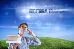 Vocational education against green hill under blue sky. The word vocational education and geeky student holding a pile of books against green hill under blue sky Royalty Free Stock Photography