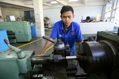 Vocational school. Students are practices using the lathe in the city of Solo, Central Java, Indonesia Stock Photo
