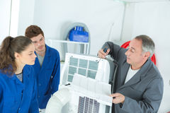 Vocational students learns air conditioning repair from experienced instructor Royalty Free Stock Image