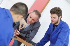 Vocational teacher with students. Teacher stock photos