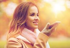 Voce della registrazione della donna sullo smartphone nel parco di autunno Fotografia Stock