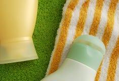 Vochtinbrengende crèmen en badhanddoeken Stock Foto