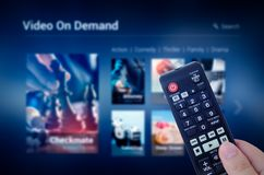 VOD service screen with remote control in hand Stock Images