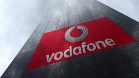 Vodafone-embleem op een wolkenkrabbervoorgevel die op wolken wijzen Het redactie 3D teruggeven Stock Foto