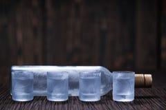 Vodca congelada no vidro pequeno na tabela de madeira, foco seletivo Imagens de Stock