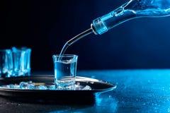 A vodca derramada em um vidro iluminou-se com luminoso azul imagem de stock royalty free