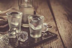 Vodca em vidros de tiro no fundo de madeira rústico Foto de Stock Royalty Free