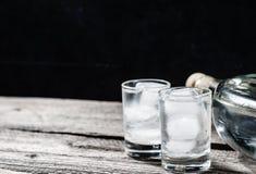 Vodca fria em vidros de tiro em um fundo preto Imagens de Stock