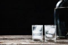 Vodca fria em vidros de tiro em um fundo preto Foto de Stock